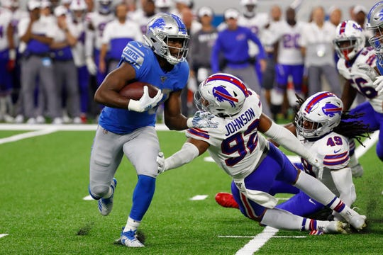Detroit Lions running back Kerryon Johnson (33) avoids the tackle of Buffalo Bills defensive end Darryl Johnson (92).
