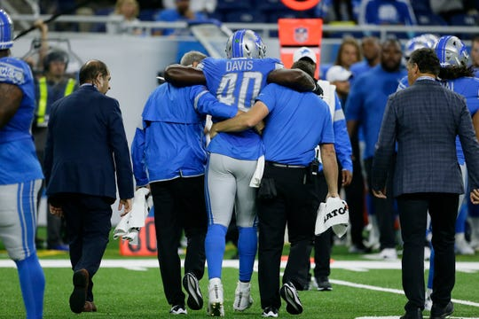 Detroit Lions middle linebacker Jarrad Davis (40) is helped off the field by medical staff in the first half.