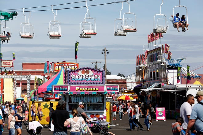 A man gestures toward an attaction while riding the fair lift above the Oregon State Fair in Salem, Oregon, on Saturday, Aug. 24, 2019.