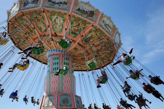 Fairgoers ride the swing carousel at the Oregon State Fair in Salem, Oregon, on Saturday, Aug. 24, 2019.