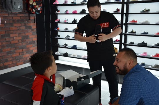 Miguel Rubio, 34, helps Sánchez student Edwin Lopez pick shoes at Shoe Pavillion in the Northridge Mall. Rubio and his friends Juan del Real, Jorge Edeza, and Sergio Ceja financed a back-to-school shopping spree for 66 students of Jesse G. Sánchez Elementary in the Alisal Union School District.