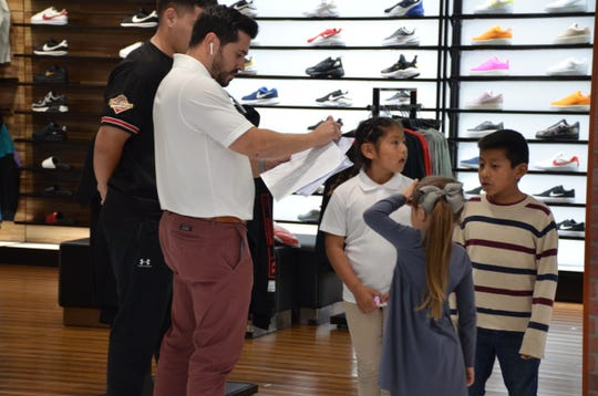 Jorge Edeza, a former student of Sánchez Elementary, helps students Carlos Mendez and Alison Acosta pick shoes at Shoe Pavillion during a back-to-school shopping spree he helped finance with his friends Juan del Real, Miguel Rubio and Sergio Ceja.