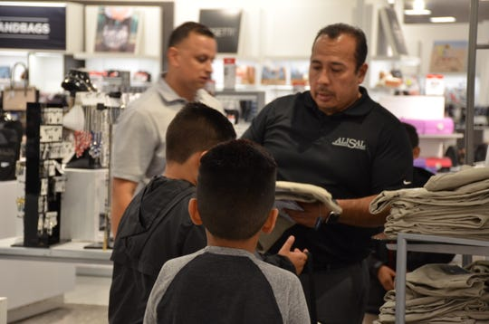 Jesse G. Sánchez Elementary Principal Roberto Rodriguez helps two students pick clothes during a back-to-school shopping spree that took place Friday, Aug. 24., at the Northridge Shopping Center in Salinas.