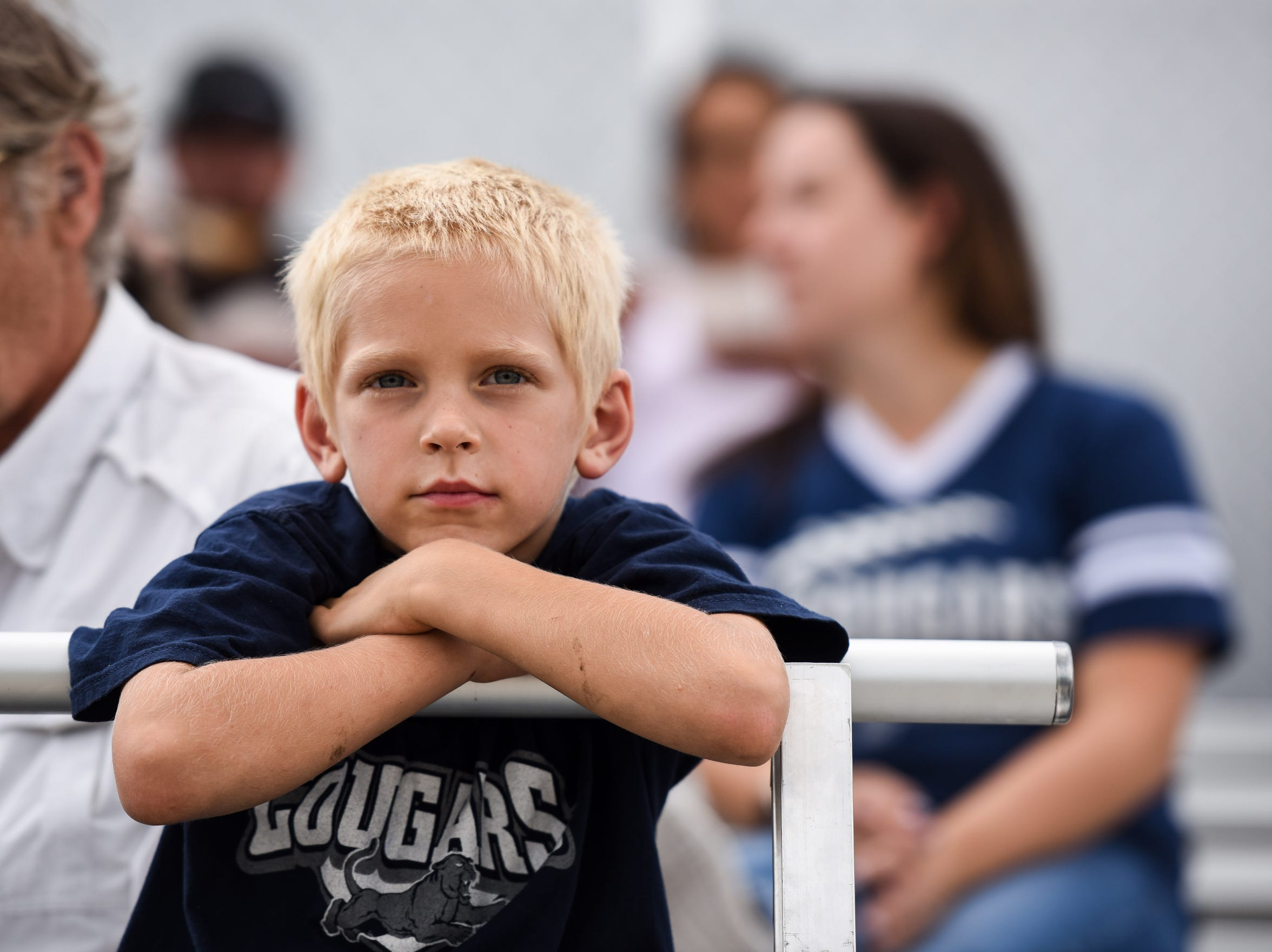 Michael Haugen, 6, watches Burke High School football team before the game at Tolstedt field, Friday, Aug. 23.