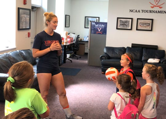 UVA senior Jenn Wineholt shows Aida Aleshire (with ball) and her friends the volleyball team room at Memorial Gym.