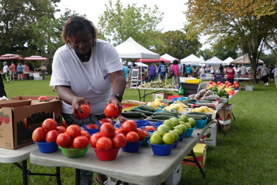 Crystal Holt, who sells fresh produce from Fresh Basket Produce at the Tallahassee Farmers Market, fills up bowls with tomatoes for customers.