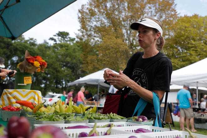 Stephanie Pohler buys produce from Handsome Harvest Farm's booth at the Tallahassee Farmers Market Saturday, Aug. 24, 2019.