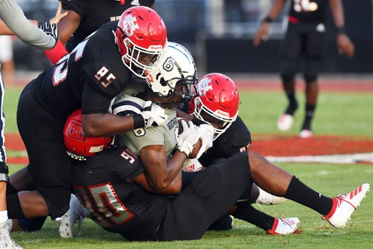 Vero Beach defenders wrap up a Delray Beach-American Heritage ball carrier during the Fighting Indians 7-3 win on Aug. 23, 2019.