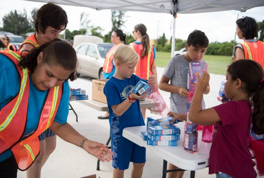 Michael DeVaney (center), 9, of Hobe Sound, volunteers with his mother alongside other children and adults as they load vehicles with food during the Treasure Coast Food Bank Mobile Pantry at the Martin County Fairgrounds on Saturday, Aug. 24, 2019, in Stuart. For more information, go to stophunger.org.