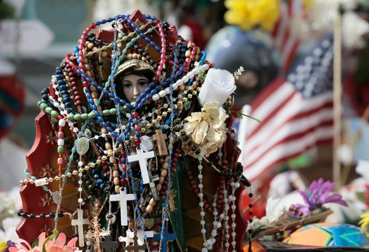 Dozens of rosaries hang from a statue of La Virgen de Guadalupe at the Walmart memorial site in East El Paso on Saturday, Aug. 24, 2019.