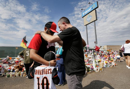 Adam Bowles, pastor of Castle Church in Norwich, Conn,, prays with Ivan Rodriguez and his son Ivan Rodriguez Jr. at the Walmart memorial site in El Paso, Texas.