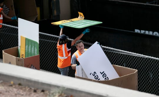 Workers begin disposing of signs from inside the Walmart store near Cielo Vista Mall where on Aug. 3, 2019, 22 El Pasoans were murdered and 25 others were wounded. The store is being renovated to be reopened.