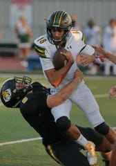 Royal High quarterback Tanner Wolfe is brought down by Ventura High's Chili Tanner in the first quarter of Friday's night's season opener. Ventura won, 51-14.