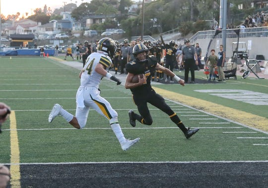 Ventura High's Cade Ledesma heads for the end zone with Royal's Nate Hamburger in hot pursuit during the Cougars' 51-14, season-opening win over Royal on Friday night.