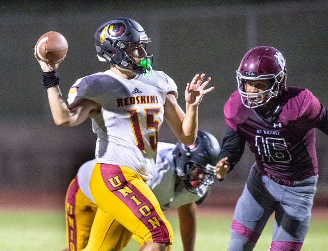 Tulare Union quarterback Jorge Gonzalez passes against Mt. Whitney defender in a non-league high school football game at Mineral King Bowl on Friday, August 23, 2019.