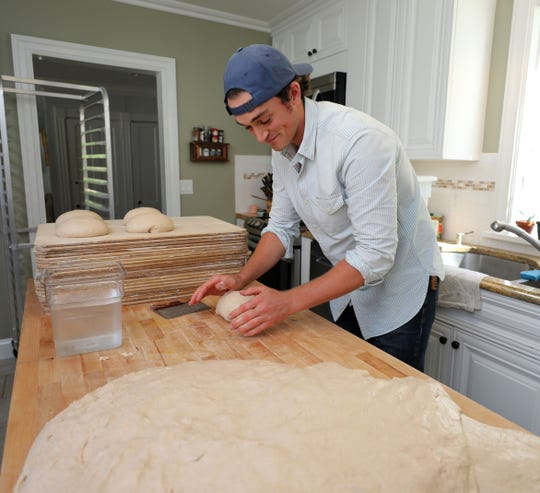 "Chase Harnett, a bread baker from Ossining, shapes loaves of bread Aug. 24, 2019. He places his mobile ""bread box"", called the Hudson Oven Bread Box in various communities, inviting people to purchase loaves of bread, using an honor system."