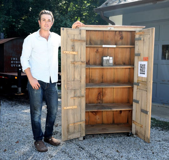 "Chase Harnett, a bread baker from Ossining, is pictured with is mobile bread box Aug. 24, 2019. He places the mobile ""bread box"", called the Hudson Oven Bread Box in various communities, inviting people to purchase loaves of bread, using an honor system."
