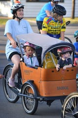 Kathryn Hager rides a cargo bike with Birdie Raeke, 3, and Maggie Hager, 2, riding in style at the start of the 38th Annual Hotter'N Hell Hundred in August 2019.