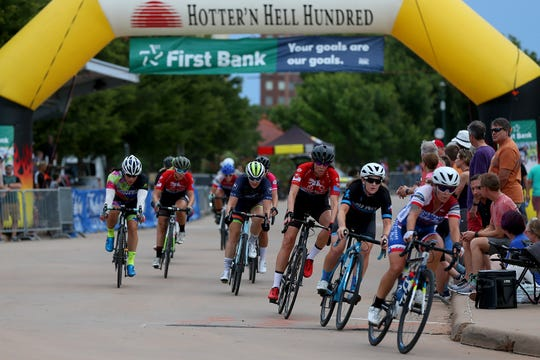 Racers ride under the HHH banner during the 2019 Hotter'N Hell Hundred Womens criterium Friday evening around the MPEC.