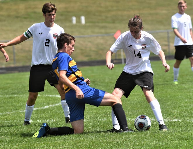 Philo's Cameron Scott and Coshocton's Aiden Stein (14) battle for possession in the Redskins' 4-3 win on Saturday.