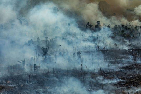 A handout photo made available by Greenpeace Brazil showing smoke rising from the fire at the Amazon forest in Novo Progresso in the state of Para, Brazil on Aug. 23, 2019.