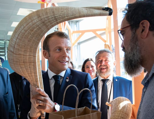 French President Emmanuel Macron holds a Chistera, a wicker glove used in the traditional Basque pelota game, as he tours the exhibition hall above the international press center on the opening day of the G7 summit, in Anglet, southwestern France, Saturday Aug.24, 2019. U.S. President Donald Trump and the six other leaders of the Group of Seven nations will begin meeting Saturday for three days in the southwestern French resort town of Biarritz.