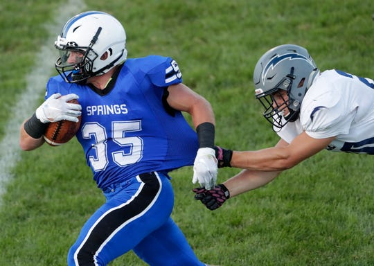 St. Mary's Springs' Marcus Orlandoni (35) tries to break away from Lake Country Lutheran's Andrew Schumacher during their football game at Fruth Field on Saturday in Fond du Lac.