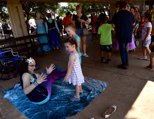 Mermaid Jill D'Entremont tells a fish story to a pair of young fans Saturday at Nelson Park Festival Gardens
