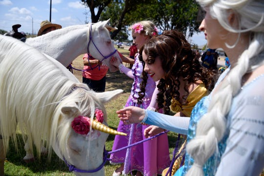 Disney character princesses greet two members of Hardin-Simmons University's Six White Horses Saturday at Nelson Park Festival Gardens.