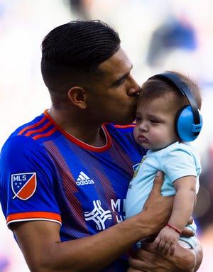 FC Cincinnati midfielder Victor Ulloa (8) kisses his child before the MLS match between FC Cincinnati and Columbus Crew SC on Sunday, Aug. 15, 2019, in Cincinnati.