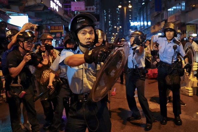 A policeman points his gun after confronting demonstrators during a protest in Hong Kong, Sunday.