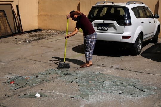 A man sweeps broken glass near the 11th-floor building that houses the media office in a stronghold of the Lebanese Hezbollah group, in a southern suburb of Beirut, Lebanon, Sunday.