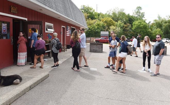 People line up to enter Parmenter's Northville Cider Mill on Sunday.