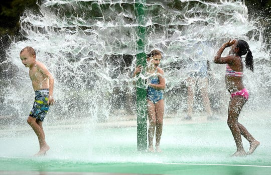 Children splash in the new splash pad at Riverview Park in North Augusta, S.C., Monday.