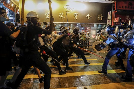 Policemen clash with demonstrators on a street in Hong Kong, Sunday.