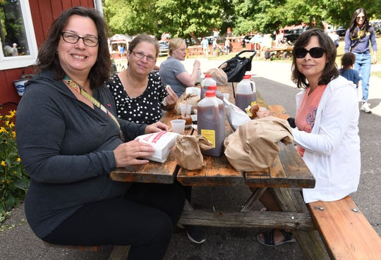 Sisters, Tammy Bridges, left, of Madison Heights, Lesa Eickholdt of Madison Heights, and Debbie Mifsud of Northville, enjoy cider and donuts at Parmenter's Northville Cider Mill.