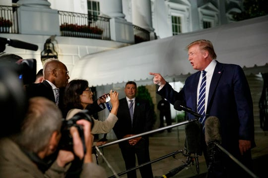 President Donald Trump speaks with reporters as he walks to Marine One on the South Lawn of the White House, Friday.