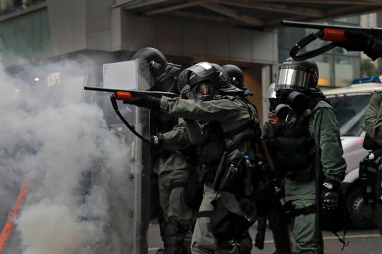 Riot policemen point weapons during a confrontation with demonstrators in Hong Kong, Sunday.
