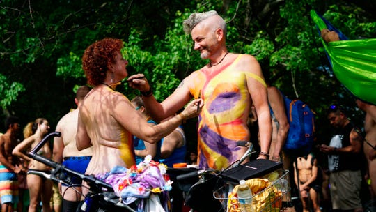 In this photo provided by David Cimetta, Melanie and Jim O'Connor paint each other's nude body while standing next to their bicycles before the start of the Philly Naked Bike Ride in Philadelphia on Saturday Aug. 24, 2019.
