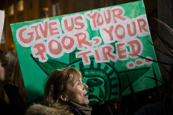 A protestor holds up a sign quoting the poem engraved on the Statue of Liberty.
