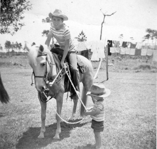 Robert Ballard is pictured in  1957 on a horse named Snow. His brother, David, holds the reins.