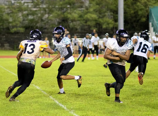 John F. Kennedy High's Quintin Kakas hands off the ball to Jacobe Quinata during the first half of the high school football game against the Southern Dolphins at JFK field Aug. 24, 2019. JFK won 7-0.