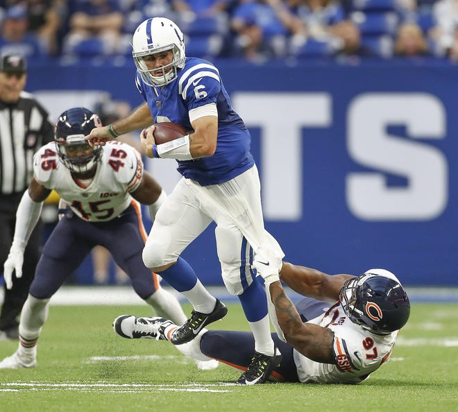 Indianapolis Colts quarterback Chad Kelly (6) runs over Chicago Bears defensive tackle Nick Williams (97) in the second quarter of their preseason game at Lucas Oil Stadium on Saturday, Aug 24, 2019.