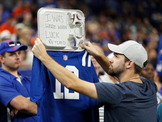 Josh Wilmore holds up a sign saying he was at the game when everyone found out that Colts quarterback Andrew had retired. It was a Colts-Bears preseason game on Saturday at Lucas Oil Stadium.