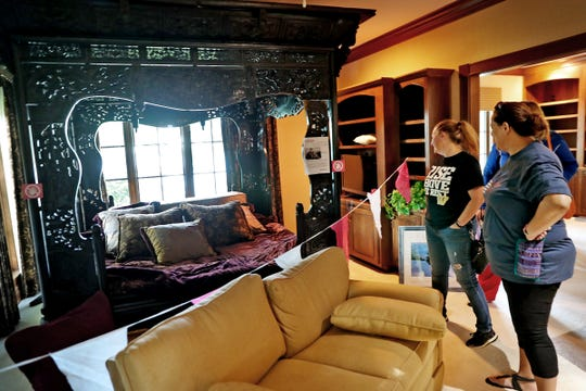 People look at a one-of-a-kind Oriental hand-carved bed that was orignally owned by Johnny Cash and June Carter, seen for sale at an estate sale in the Indianapolis home on Geist, at 11707 Landings Dr., Sunday, Aug. 25, 2019.  Aether Estate Sales ran the three-day sale which included Johnny Cash's bed, Peter Max Lithographs, Pablo Picasso Lithographs, Albert Einstein personal documents, and more. Many household furnishings also were for sale.