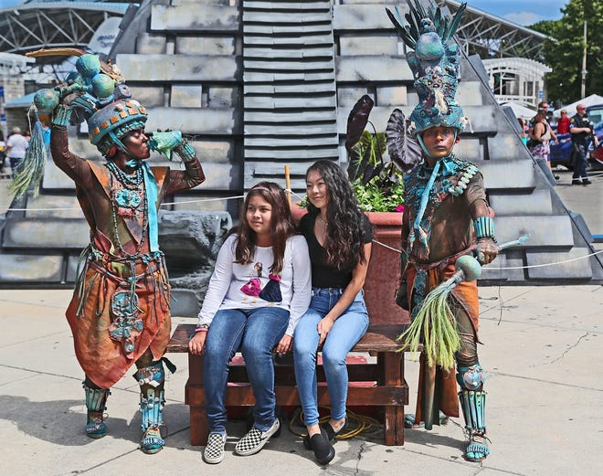 Naomi Martinez, left, and Gao Her, 17, both of Milwaukee, pose for a photo with actors dressed as ancient Mayans in front of a a replica stone pyramid temple during Milwaukee's Mexican Fiesta in 2019.