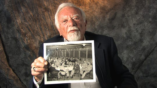 In this 2009 file photo, Paul Melrood shows a photo of himself  with the 53rd Air Group at MacDill Air Field in Tampa, Florida, with a table setting they recovered from a ship sunk off the Florida coast by a German U-Boat.  Melrood went from private to officer training school during his time in the Army Air Corp.