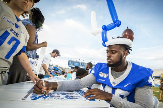 MTSU's Avery Jones (40) signs a fan's poster during the Blue Raiders Fan Night on August 24, 2019.