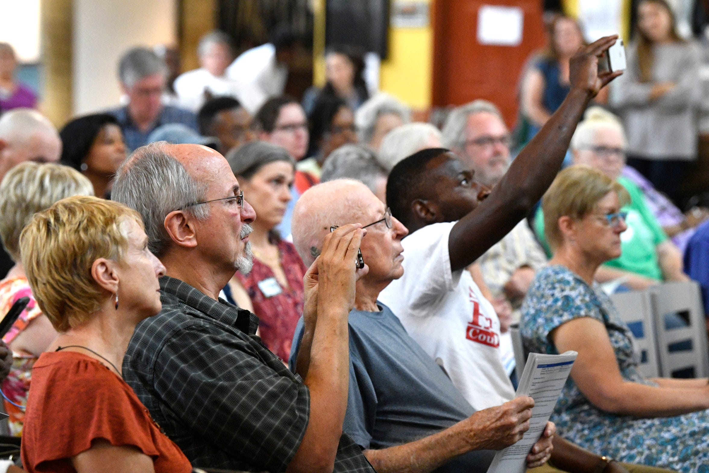 Audience members take photos and videos as the candidates speak at a forum for the 8 at-large Metro Nashville runoff candidates at the Nashville Farmers Market. Sunday, Aug. 25, 2019, in Nashville, Tenn.