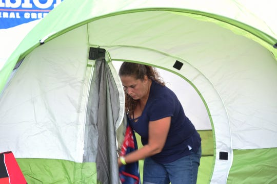 The Emerson Police Dept Community  hosted its annual open house and movie night together with a free overnight family campout for Emerson residents. Here, Karen Blanken works on her tent.